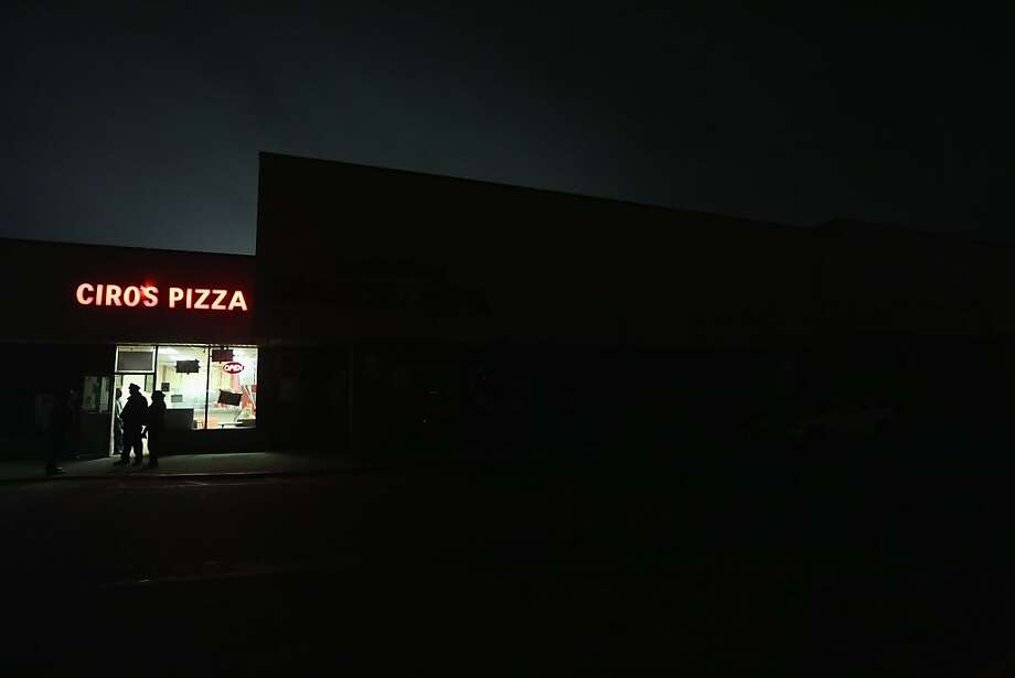 A pizza shop is open next to a darkened supermarket in the Rockaway neighborhood on November 12, 2012 in the Queens borough of New York City. The area was hard hit by Superstorm Sandy and power remains out in many places while a few businesses have reopened. Photo: Mario Tama, Getty Images