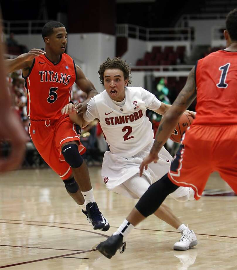 Aaron Bright drives the ball past Fullerton's Kwame Vaughn in the first period. The Stanford men's basketball team played the Fullerton Titans at Maples Pavilion in Stanford, Calif., on Monday, November 12, 2012. Stanford won 81-68 Photo: Carlos Avila Gonzalez, The Chronicle