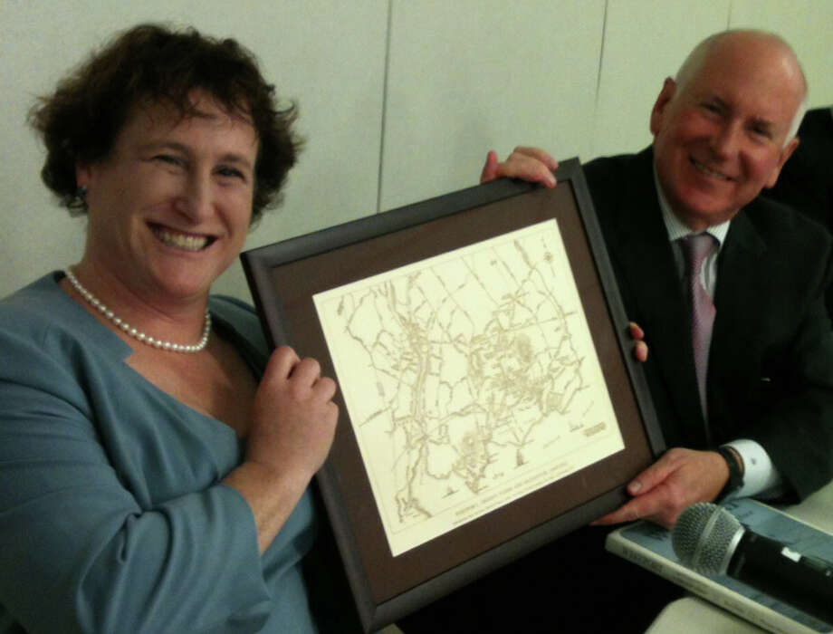 Elaine Whitney, elected as the new chairwoman of the Board of Education on Monday night, presents a map of the town of Westport to James Marpe, outgoing acting chairman of the board, as he stepped down from the panel.  Westport CT 11/12/12 Photo: Andrew Brophy / Westport News contributed