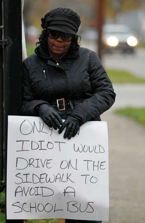 Shena Hardin holds up a sign to serve a highly public sentence Tuesday, Nov. 13, 2012, in Cleveland, for driving on a sidewalk to avoid a Cleveland school bus that was unloading children. A Cleveland Municipal Court judge ordered 32-year-old Hardin to serve the highly public sentence for one hour Tuesday and Wednesday. (AP Photo/Tony Dejak) Photo: Tony Dejak / AP