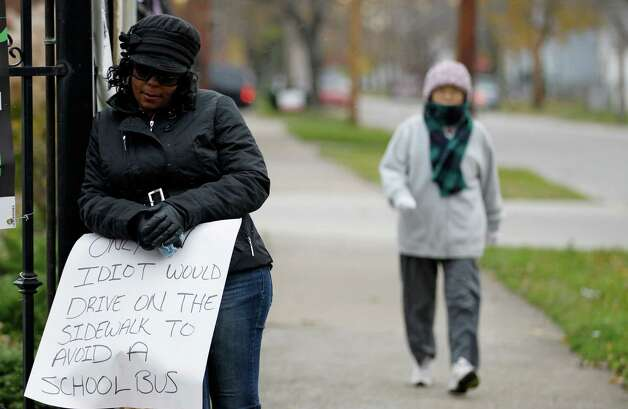A woman walks by as Shena Hardin, left,  holds up a sign  to serve a highly public sentence Tuesday, Nov. 13, 2012, in Cleveland. Hardin was caught on camera driving on a sidewalk to avoid a Cleveland school bus that was unloading children.  A Cleveland Municipal Court judge ordered 32-year-old Hardin to serve the highly public sentence for one hour Tuesday and Wednesday.(AP Photo/Tony Dejak) Photo: Tony Dejak / AP