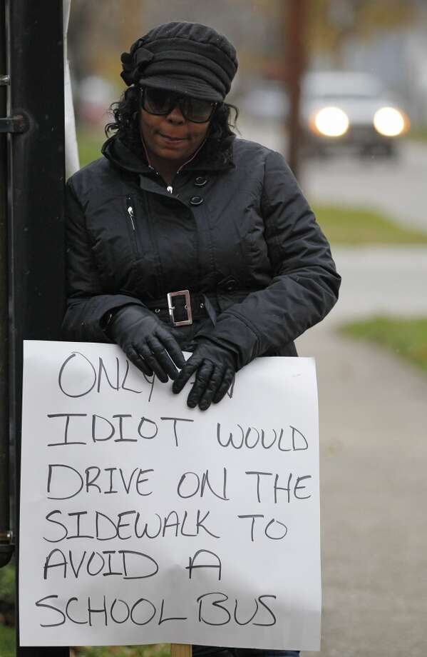 Shena Hardin holds up a sign to serve a highly public sentence Tuesday, Nov. 13, 2012, in Cleveland, for driving on a sidewalk to avoid a Cleveland school bus that was unloading children. A Cleveland Municipal Court judge ordered 32-year-old Hardin to serve the highly public sentence for one hour Tuesday and Wednesday. (AP Photo/Tony Dejak) (AP)