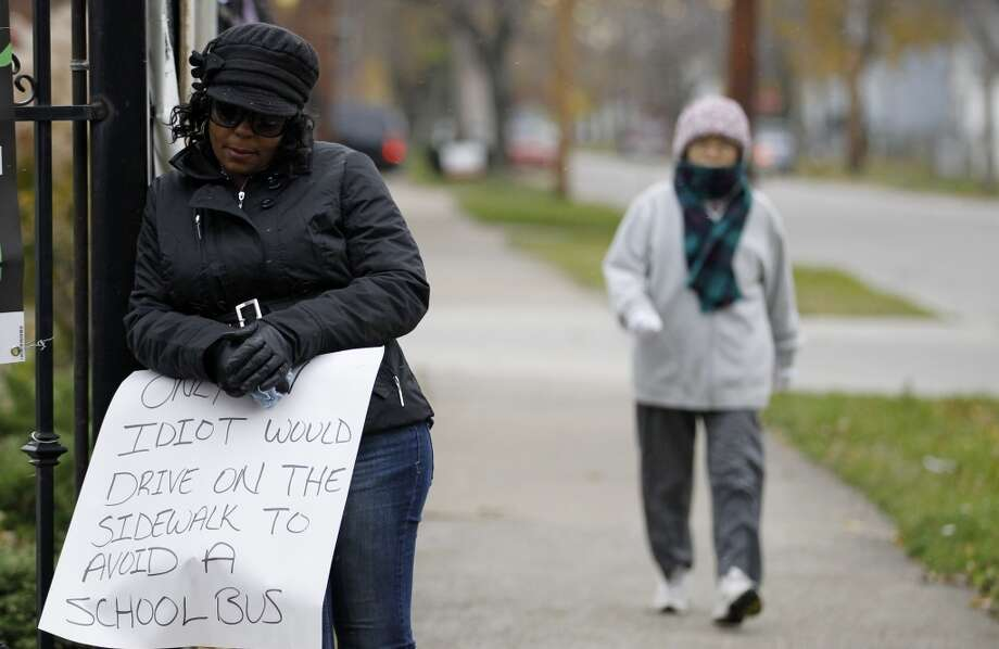 A woman walks by as Shena Hardin, left,  holds up a sign  to serve a highly public sentence Tuesday, Nov. 13, 2012, in Cleveland. Hardin was caught on camera driving on a sidewalk to avoid a Cleveland school bus that was unloading children.  A Cleveland Municipal Court judge ordered 32-year-old Hardin to serve the highly public sentence for one hour Tuesday and Wednesday.(AP Photo/Tony Dejak) (AP)