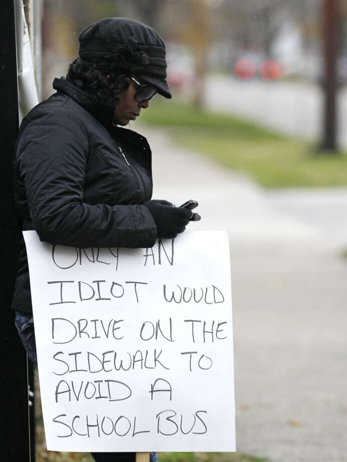 Shena Hardin checks her cell phone as she holds up a sign to serve a highly public sentence Tuesday, Nov. 13, 2012, in Cleveland, for driving on a sidewalk to avoid a Cleveland school bus that was unloading children. A Cleveland Municipal Court judge ordered 32-year-old Hardin to serve the highly public sentence for one hour Tuesday and Wednesday. (AP Photo/Tony Dejak) (AP)