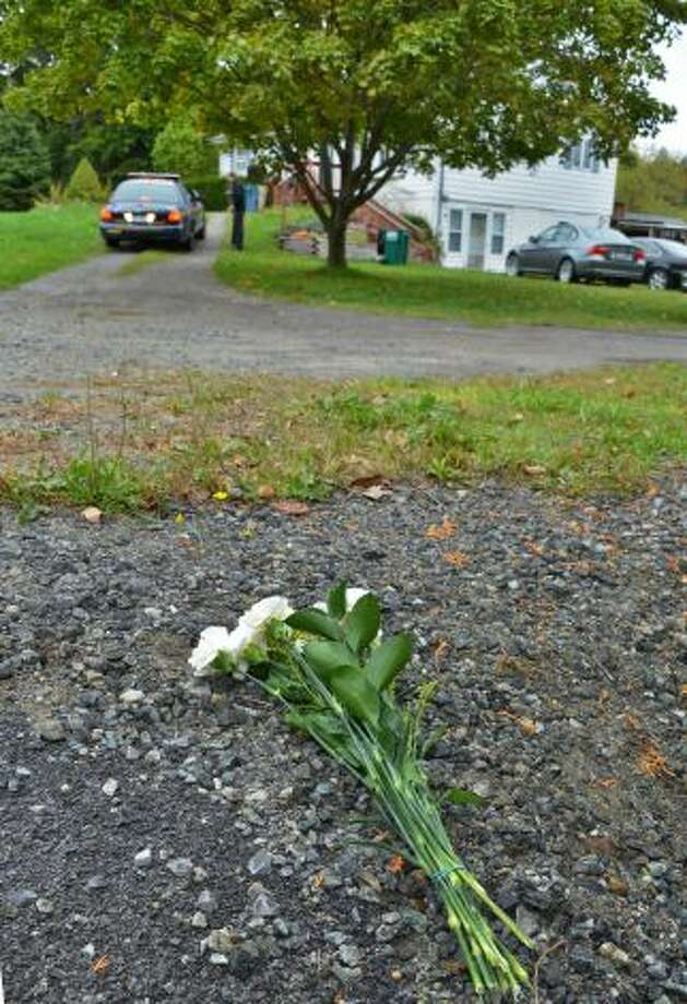Flowers placed at the bottom of the driveway Tuesday Oct. 2, 2012, where 11-year-old Lane Rowe died after he tried to stop a minivan that was rolling backward with his siblings inside on Blue Barns Road in the town of Ballston. (John Carl D'Annibale / Times Union)