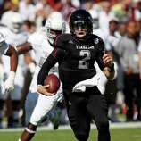 In this Nov. 3, 2012 photograph, Texas A&M quarterback Johnny Manziel (2) runs past Mississippi State defenders in their NCAA college football game in Starkville, Miss. No. 16 Texas A&M won 38-13. (AP Photo/Rogelio V. Solis)
