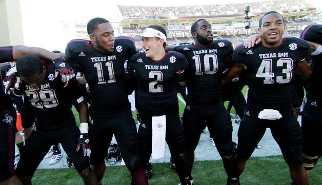 Decked out in black, A&M's Johnny Manziel (2) joins Jonathan Stewart (11), Sean Porter (10) and Justin Bass (43) in singing their fight song after the win over Mississippi State. Photo: Rogelio V. Solis, Associated Press