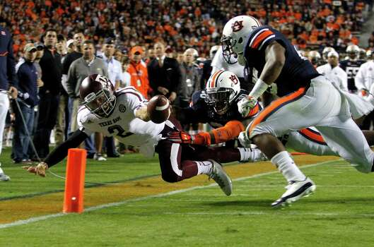 Texas A&M quarterback Johnny Manziel (2) dives for the end zone for a touchdown past Auburn linebacker Cassanova McKinzy (30) and Auburn linebacker Daren Bates (25) during the first half of an NCAA college football game on Saturday, Oct. 27, 2012, in Auburn, Ala. (AP Photo/Butch Dill) Photo: Butch Dill, Associated Press / FR111446 AP