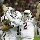 Texas A&M quarterback Johnny Manziel (2) reacts as he and teammates celebrate a win over top ranked Alabama during an NCAA college football game at Bryant-Denny Stadium in Tuscaloosa, Ala., Saturday, Nov. 10, 2012. Texas A&M won 29-24. (AP Photo/Dave Martin)