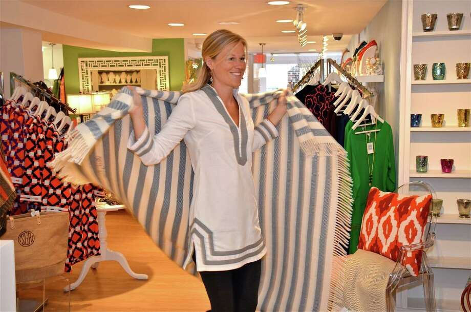 Sheila Grow, owner of She la la on Main Street, twirls around in an ultra-soft custom monogrammed throw blanket that she sells in her store.  Oct. 16, 2012, New Canaan, Conn. Photo: Jeanna Petersen Shepard