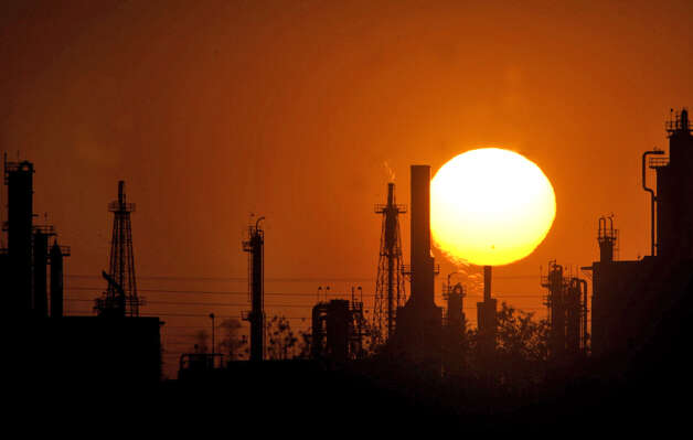 "In this Tuesday, Aug. 21, 2007 file photo, the sun sets behind an oil refinery on Rosedale Highway, in Bakersfield, Calif. On Wednesday, Nov. 14, 2012, California's largest greenhouse gas emitters will for the first time begin buying permits in a landmark ""cap-and-trade"" system meant to control emissions of heat-trapping gases and spur investment in clean technologies. The program is a key part of California's 2006 climate-change law, AB32, a suite of regulations that dictate standards for cleaner-burning fuels, more efficient automobiles and increased use of renewable energy. (AP Photo/The Bakersfield Californian, Casey Christie) MANDATORY CREDIT, NO MAGS, NO SALES, TV OUT, ONLINE OUT Photo: Casey Christie, Associated Press"