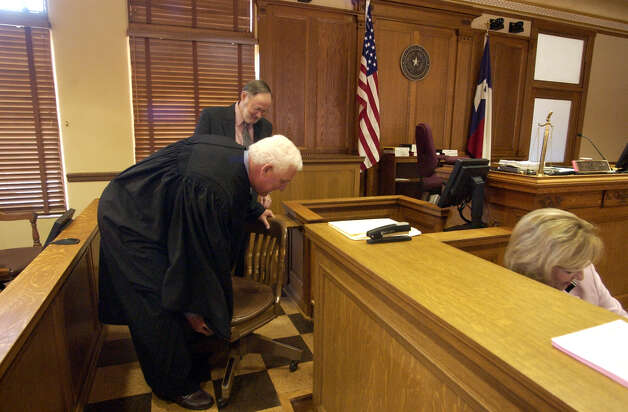 Judge John J. Specia lifts a chair into the witness box during the first day of business since restoration work began on the 225th District court at the Bexar County courthouse. The judge called a witness to testify and discovered there was no chair for him to sit in, just one of many minor glitches going on in the newly restored court room. JOHN DAVENPORT / STAFF Photo: JOHN DAVENPORT, SAN ANTONIO EXPRESS-NEWS / SAN ANTONIO EXPRESS-NEWS