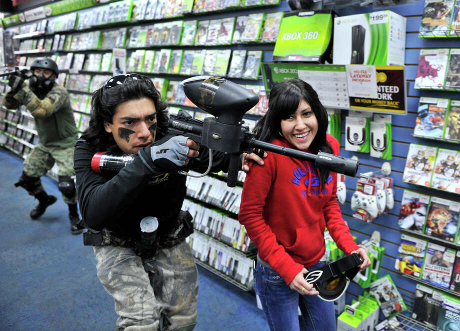 "Isaac Barriente of PaintBallOps San Antonio (left) ""covers"" Alyssa Garcia (red shirt) as she enters the GameStop store at 76635 NW Loop 410 to receive first copy of Call of Duty Black Ops2 shortly after midnight Tuesday morning. Photo: Robin Jerstad/For The Express-Ne"