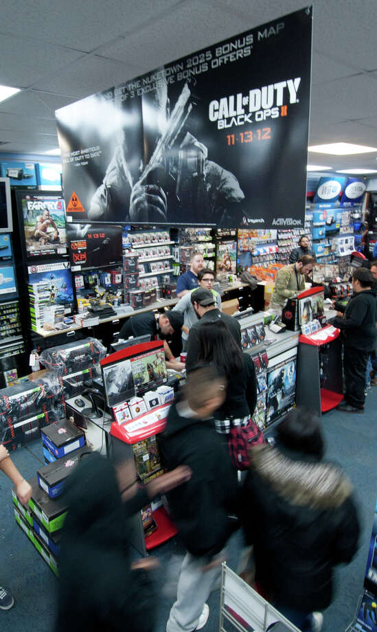 Customers head to the cashiers shortly after midnight Tuesday morning with their copies of Call of Duty Black Ops 2 at the 7635 NW Loop 410 GameStop store Photo: Robin Jerstad/For The Express-Ne