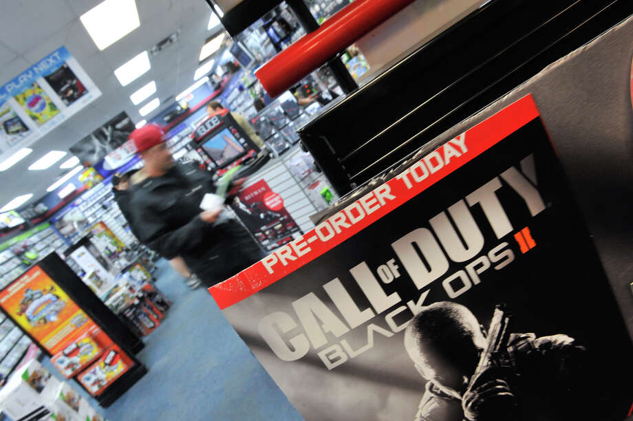 Customers leave the 7635 NW Loop 410 GameStop store shortly after midnight Tuesday morning with their copies of Call of Duty Black Ops 2. Photo: Robin Jerstad/For The Express-Ne