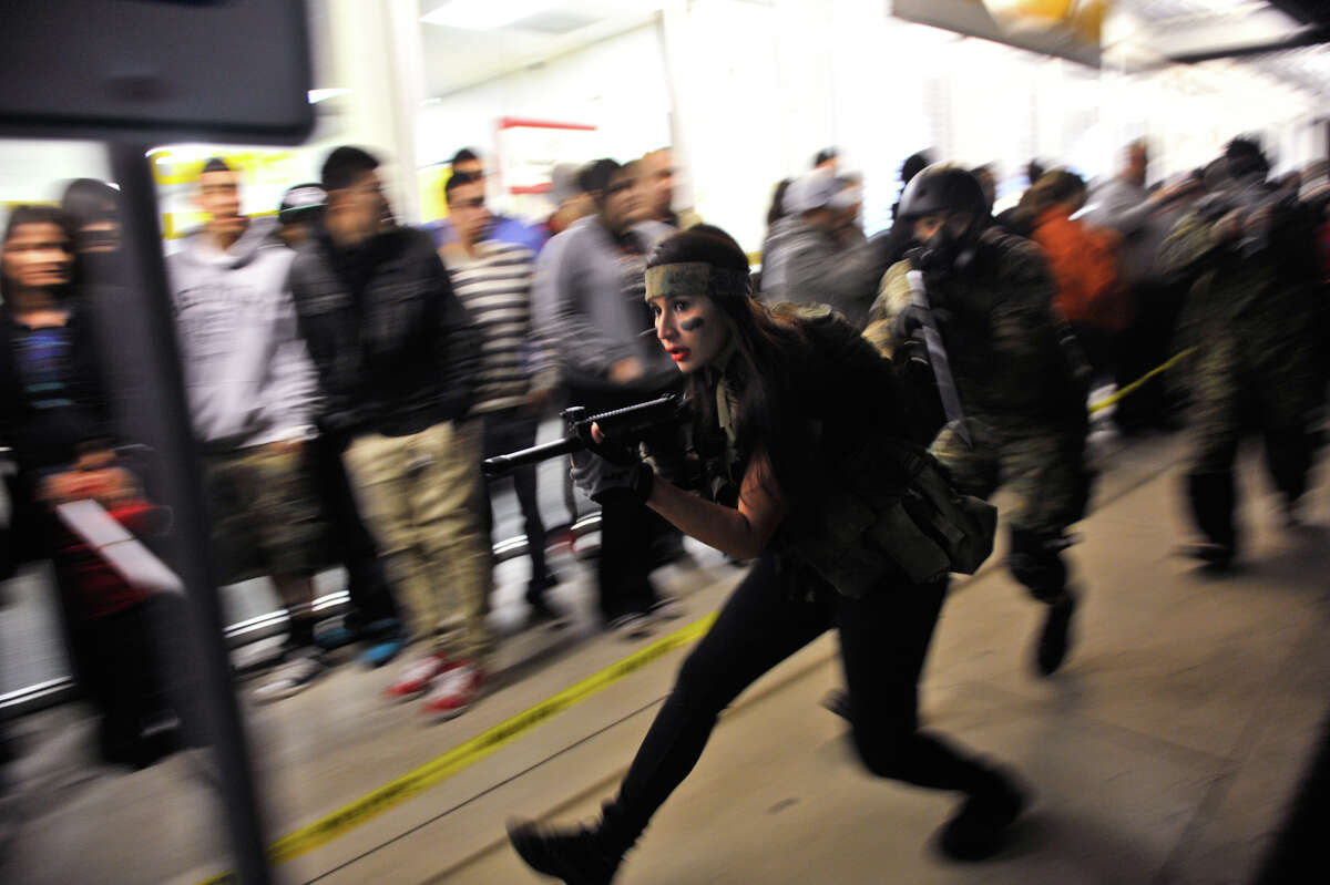 Kristen De la Rosa leads PaintBallOps San Antonio around the crowds lined up to receive their copies of Call of Duty Black Ops2 shortly before midnight Monday. De la Rosa was part of a promotion for the GameStop store at 7635 NW Loop 410 for the release of the game.