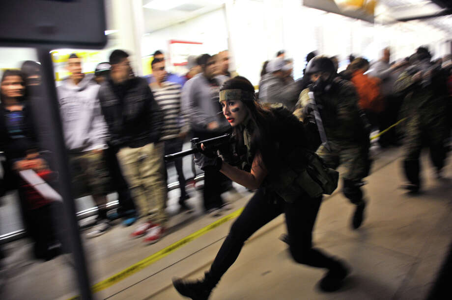 Kristen De la Rosa leads PaintBallOps San Antonio around the crowds lined up to receive their copies of Call of Duty Black Ops2 shortly before midnight Monday. De la Rosa was part of a promotion for the GameStop store at 7635 NW Loop 410 for the release of the game. Photo: For The Express-News, Robin Jerstad
