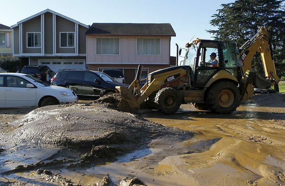 Heavy machinery scoops up mud on Lausanne Avenue and Clayton Court after a mudslide rolled through a neighborhood following a water line break from a hilltop reservoir in Daly City, Calif. on Tuesday, Nov. 13, 2012. Photo: Paul Chinn, The Chronicle