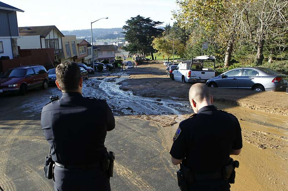 Police officers stand at the top of Lausanne Avenue while public works and water crews clean up a river of mud that rolled through a neighborhood after a water line break from a hilltop reservoir in Daly City, Calif. on Tuesday, Nov. 13, 2012. Photo: Paul Chinn, The Chronicle