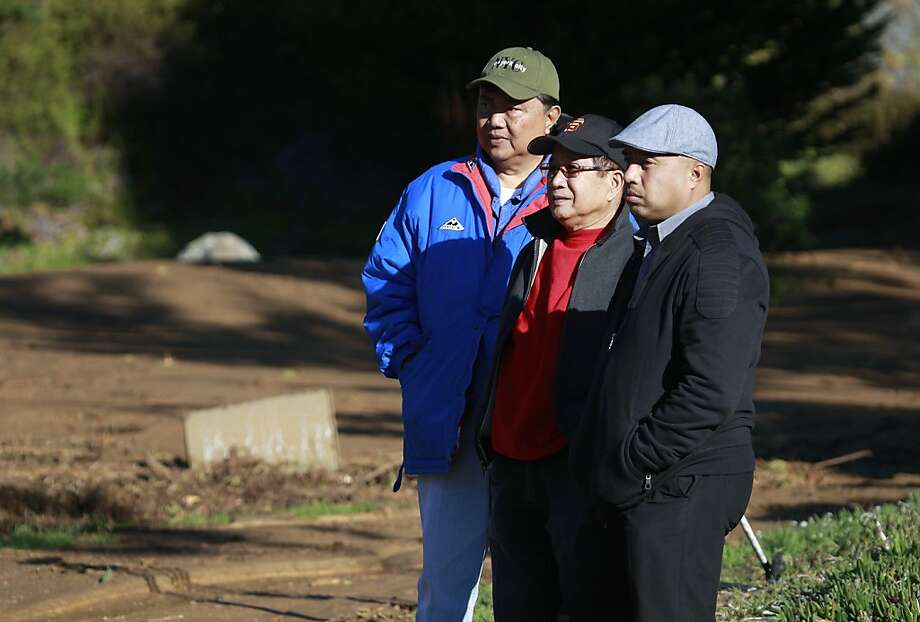 Neighborhood residents Arturo Romero (left), Ruben Postrada (center) and Joel Perez watch public works and water crews clean up a mudslide on Lausanne Avenue after a water line break from a hilltop reservoir in Daly City, Calif. on Tuesday, Nov. 13, 2012. Photo: Paul Chinn, The Chronicle