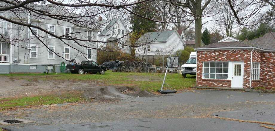 A developer wants to tear down the two-family house, to the left, and the brick building on the right to build a three-story building for both commerical and residential use. Fairfield, CT 11/13/12 Photo: Genevieve Reilly / Fairfield Citizen