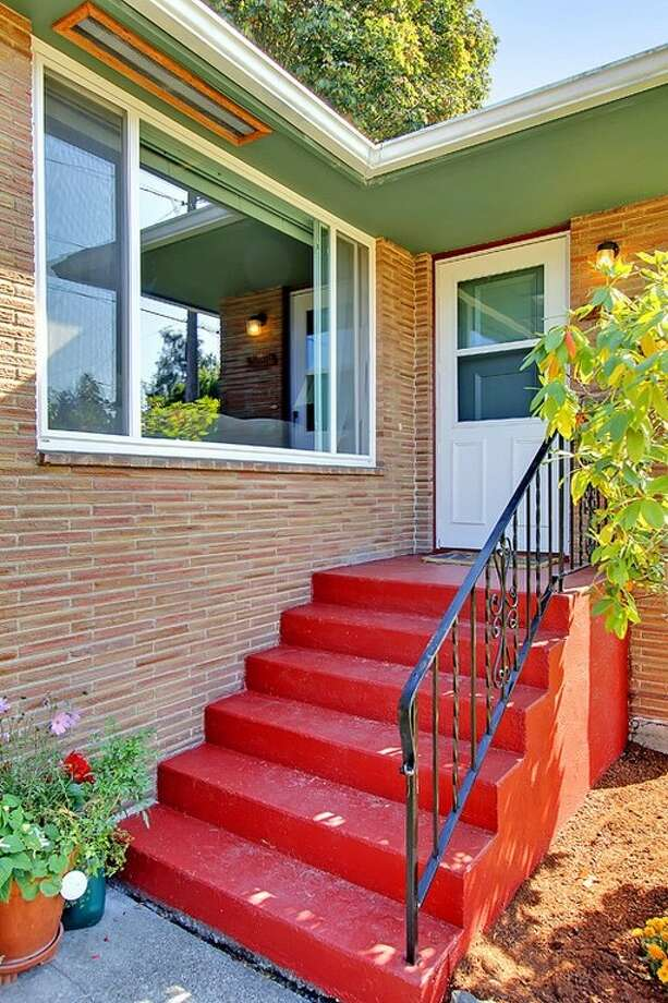 Entry of 7024 25 Ave. N.E. The 2,080-square-foot mid-century-modern brick house, built in 1954, has three bedrooms, two bathrooms and a downstairs rec room with a fireplace on a 5,100-square-foot lot. It's listed for $435,000. Photo: Tucker English,  Courtesy Corey Robinson/Keller Williams