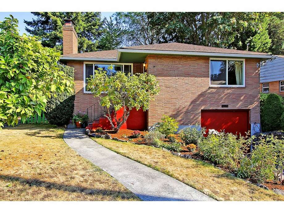 Want to live in the heart of Northeast Seattle for less than $450,000? Check out these three homes in Ravenna, starting with 7024 25 Ave. N.E. The 2,080-square-foot mid-century-modern brick house, built in 1954, has three bedrooms, two bathrooms and a downstairs rec room with a fireplace on a 5,100-square-foot lot. It's listed for $435,000. Photo: Tucker English,  Courtesy Corey Robinson/Keller Williams