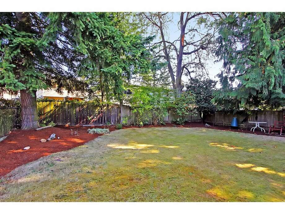 Yard of 7024 25 Ave. N.E. The 2,080-square-foot mid-century-modern brick house, built in 1954, has three bedrooms, two bathrooms and a downstairs rec room with a fireplace on a 5,100-square-foot lot. It's listed for $435,000. Photo: Tucker English,  Courtesy Corey Robinson/Keller Williams