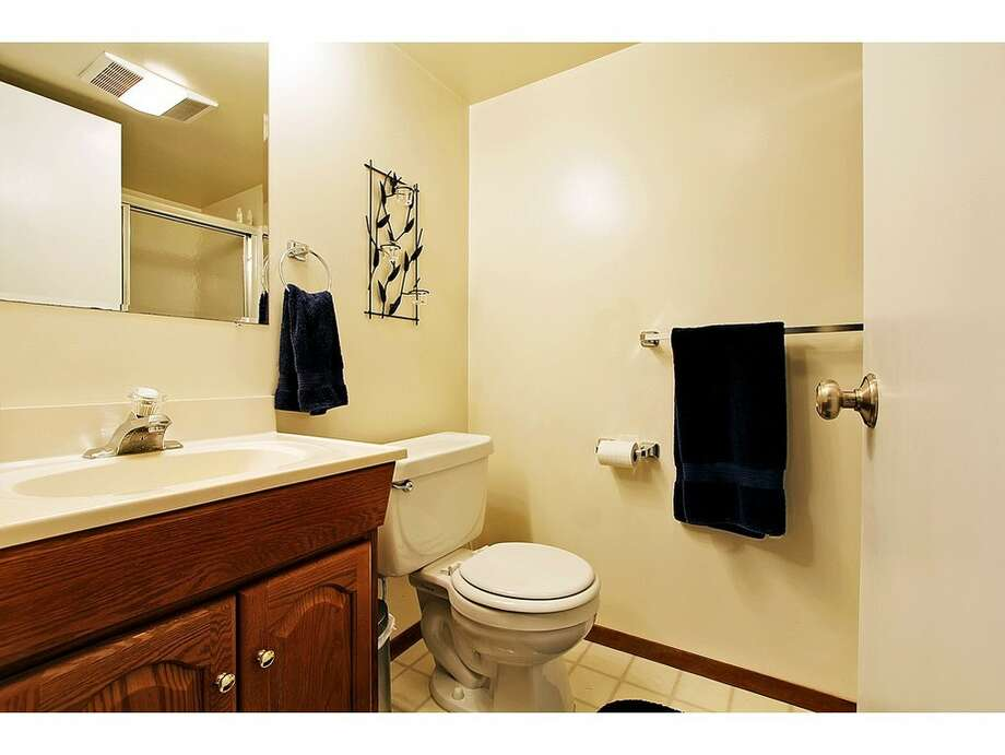 Downstairs bathroom of 7024 25 Ave. N.E. The 2,080-square-foot mid-century-modern brick house, built in 1954, has three bedrooms, two bathrooms and a downstairs rec room with a fireplace on a 5,100-square-foot lot. It's listed for $435,000. Photo: Tucker English,  Courtesy Corey Robinson/Keller Williams