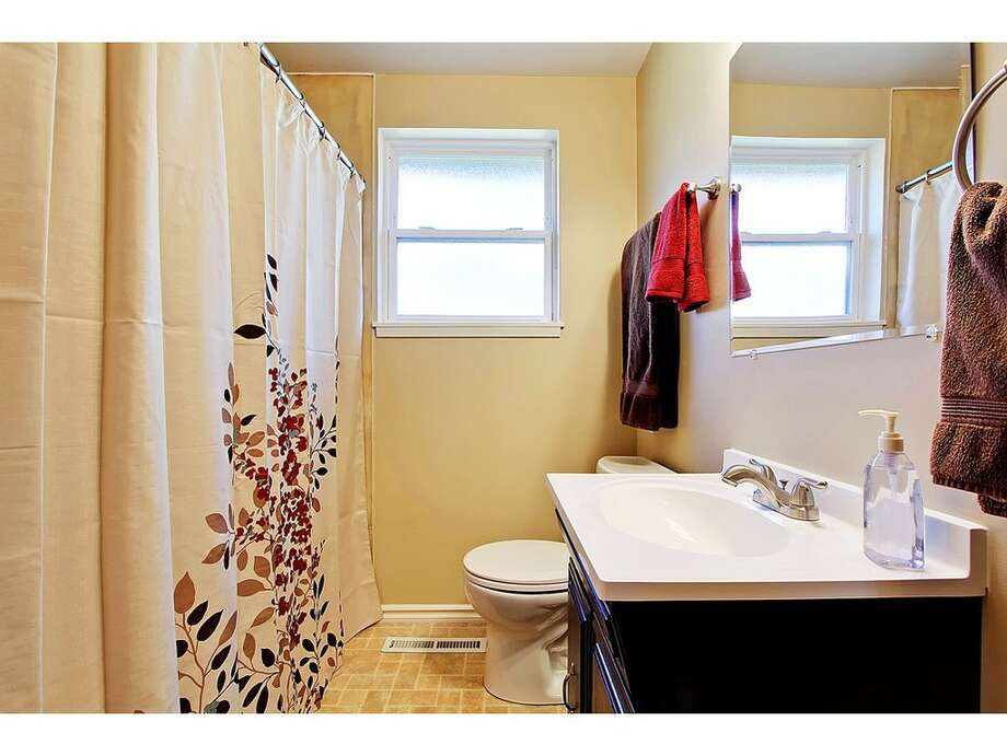 Bathroom of 7024 25 Ave. N.E. The 2,080-square-foot mid-century-modern brick house, built in 1954, has three bedrooms, two bathrooms and a downstairs rec room with a fireplace on a 5,100-square-foot lot. It's listed for $435,000. Photo: Tucker English,  Courtesy Corey Robinson/Keller Williams