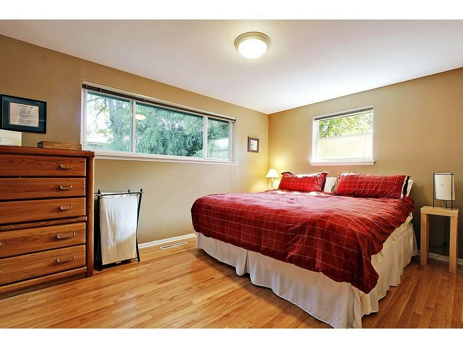Bedroom of 7024 25 Ave. N.E. The 2,080-square-foot mid-century-modern brick house, built in 1954, has three bedrooms, two bathrooms and a downstairs rec room with a fireplace on a 5,100-square-foot lot. It's listed for $435,000. Photo: Tucker English,  Courtesy Corey Robinson/Keller Williams