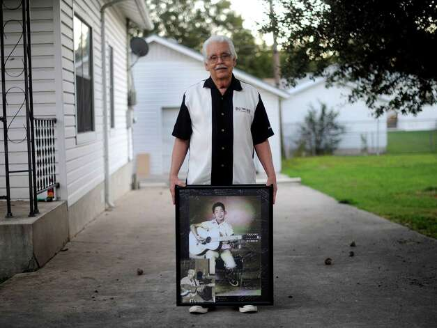 "Jesus ""Chucho"" Perales holds a cherished photo of himself, taken when he was 10 years old. In it, he poses with his prized Regal 12-string guitar. Photo: Billy Calzada, San Antonio Express-News / © 2012 San Antonio Express-News"