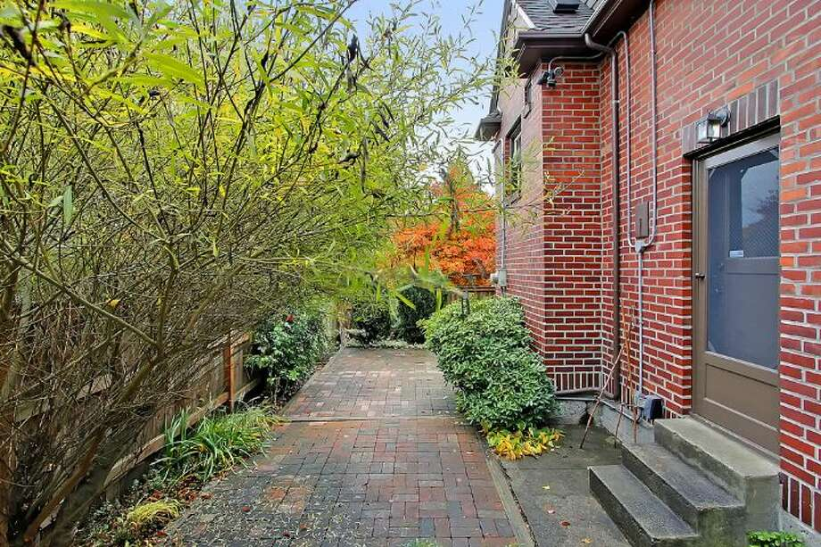 Yard of 1816 N.E. 75th St.. The 2,400-square-foot brick Tudor, built in 1929, has three bedrooms, 1.5 bathrooms, exposed-wood doors and moldings, curved doorways, a brick patio and raised garden beds on a 3,393-square-foot lot. It's listed for $450,000, although a sale is pending. Photo: Courtesy Jonathan Savage And Susan Stasik/Windermere Real Estate