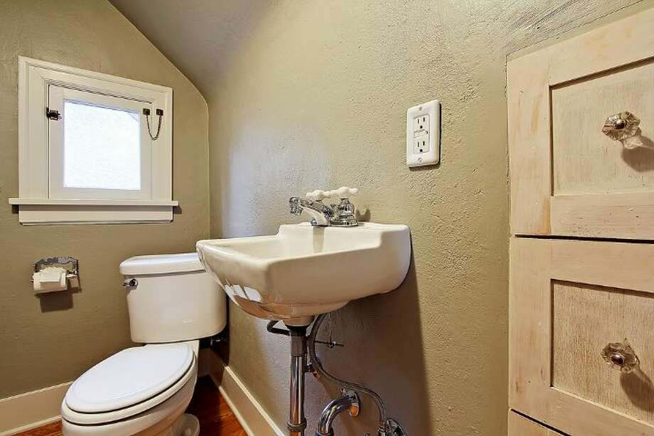 Half bathroom of 1816 N.E. 75th St.. The 2,400-square-foot brick Tudor, built in 1929, has three bedrooms, 1.5 bathrooms, exposed-wood doors and moldings, curved doorways, a brick patio and raised garden beds on a 3,393-square-foot lot. It's listed for $450,000, although a sale is pending. Photo: Courtesy Jonathan Savage And Susan Stasik/Windermere Real Estate