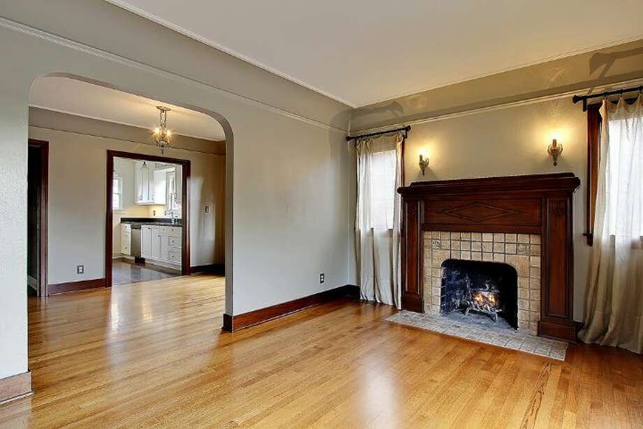 Living room of 1816 N.E. 75th St.. The 2,400-square-foot brick Tudor, built in 1929, has three bedrooms, 1.5 bathrooms, exposed-wood doors and moldings, curved doorways, a brick patio and raised garden beds on a 3,393-square-foot lot. It's listed for $450,000, although a sale is pending. Photo: Courtesy Jonathan Savage And Susan Stasik/Windermere Real Estate