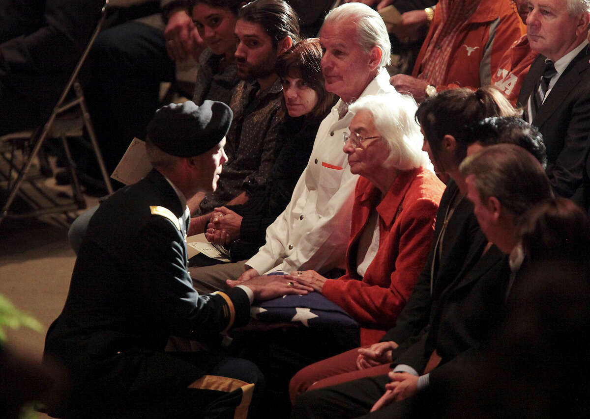 Edith Royal receives the US flag from a member of the University of Texas Army ROTC during a memorial for her husband, former University of Texas Football Coach Darrell K Royal at the Frank Erwin Center in Austin, Tuesday, Nov. 12, 2012.