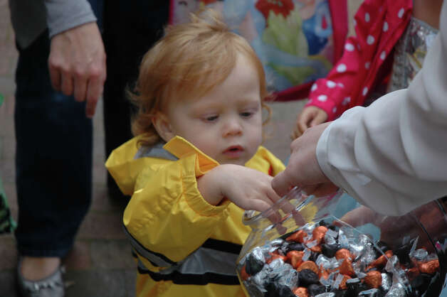 A youngster makes a careful choice of  treats during the 31st annual Halloween Parade, sponsored by the New Canaan Chamber of Commerce, on Sunday, Oct. 28. Photo: Contributed