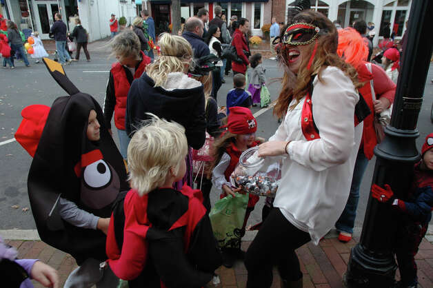 Emily Coyle, dressed as a pirate, hands out candy to eager trick-or-treaters at the 31st annual Halloween Parade, sponsored by the New Canaan Chamber of Commerce, on Sunday, Oct. 28. Photo: Contributed