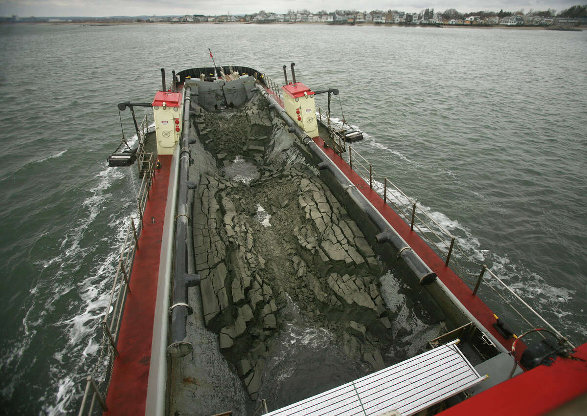 Sand dredged from the Housatonic River falls through the bottom of the vessel Currituck off Long Beach in Stratford on Tuesday, November 13, 2012.