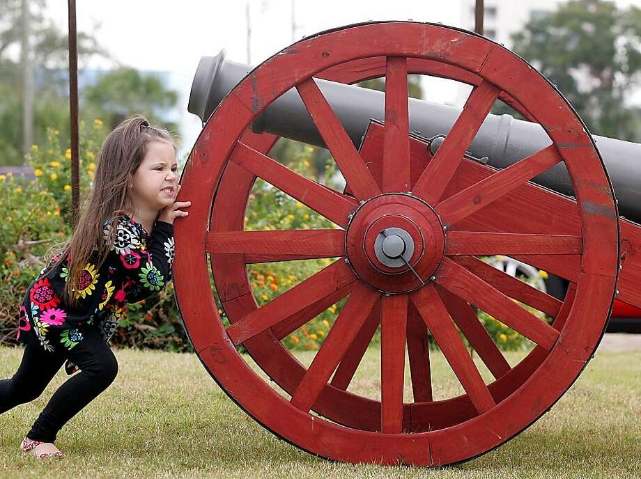 Cannon prodder:Four-year-old battery commander Lauren Timmins is determined to reposition the artillery for the Veterans Day Parade in Panama City, Fla. Photo: Andrew Wardlow, Associated Press