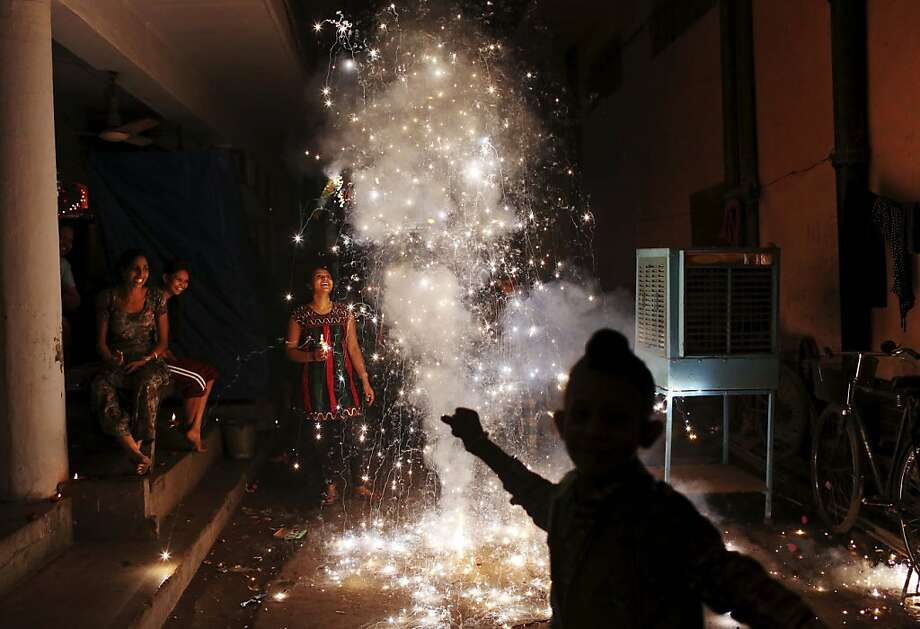 An Indian family lights firecrackers during the festival of Diwali in New Delhi, India, Tuesday, Nov. 13, 2012. The festival Diwali is an opportunity for Hindus to honour Lakshmi, the goddess of wealth and other gods. Sikhs and Jains also celebrate Diwali. Photo: Kevin Frayer, Associated Press