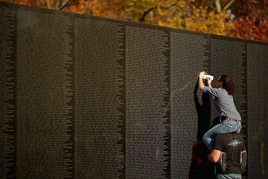 Remembering his uncle, who died in war:Kevin Palmer holds Michele Mathews on his shoulders so she can make a rubbing of the inscription of Douglas Palmer's name on the Vietnam Veterans Memorial in Washington. Douglas Palmer, Kevin's uncle, died in 1966 while serving with the Navy in Vietnam. Photo: Chip Somodevilla, Getty Images