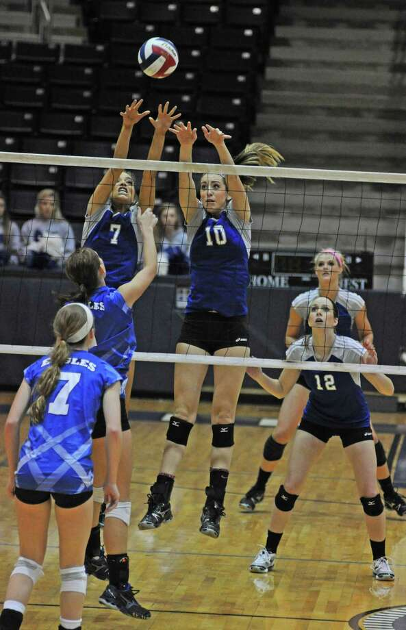 Friendswood seniors Peyton Yager (7 at net) and Shannon Ellis (10) reach for a block against Barbers Hill senior Darian Geisendorff (1) during Friendswood's 25-16, 25-15, 25-15 sweep of Barbers Hill in the Class 4A Region III volleyball finals on 11-10-12 at Coleman Coliseum. Looking on for Friendswood are seniors Shelby Carter (12) and Jill Bergeson (background). Photo: L. Scott Hainline / Chronicle
