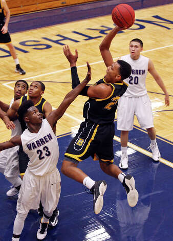Brennan's George King shoots over Warren's Demarcus Garcia during second half action Monday Nov. 12, 2012 at Paul Taylor Field House.  Warren won 82-80. Photo: Edward A. Ornelas, San Antonio Express-News / © 2012 San Antonio Express-News