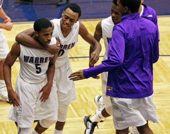Warren's Marcus Keene (left) is congratulated by teammate Warren's Paris Collins and others after the game with Brennan Monday Nov. 12, 2012 at Paul Taylor Field House.  Keene made the game winning basket. Warren won 82-80. Photo: Edward A. Ornelas, San Antonio Express-News / © 2012 San Antonio Express-News