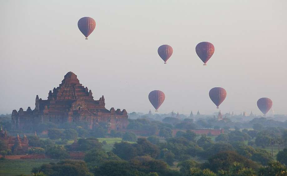 By the dawn's early flight: Hot-air balloons sail over a Buddhist temple at sunrise in Bagan, Myanmar. Photo: Mark Baker, Associated Press