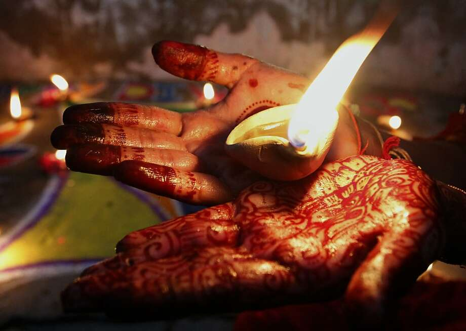 A Pakistani Hindu girl holds an earthen lamp while decorating an area of her house to celebrate Diwali, the Hindu festival of lights, Tuesday, Nov. 13, 2012 in Karachi, Pakistan. Photo: Shakil Adil, Associated Press
