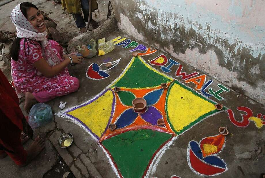 A Pakistani Hindu girl shares a laugh with her friends, not shown, as she decorates an area of her house to celebrate Diwali, the Hindu festival of lights, Tuesday, Nov. 13, 2012 in Karachi, Pakistan. Photo: Shakil Adil, Associated Press