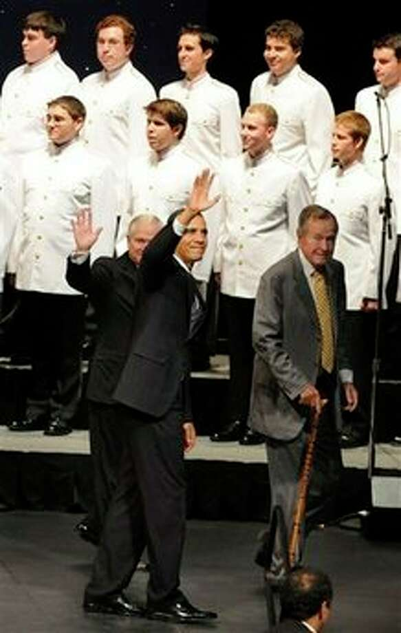 President Barack Obama, center, former President George H. W. Bush, right, and Defense Secretary Robert Gates say goodbye to the crowd at Texas A&M University where they spoke on occasion of the 20th anniversary of the Points of Light community service movement Friday, Oct. 16, 2009, in College Station, Texas.  (AP Photo/Pat Sullivan) Photo: Pat Sullivan, AP / AP