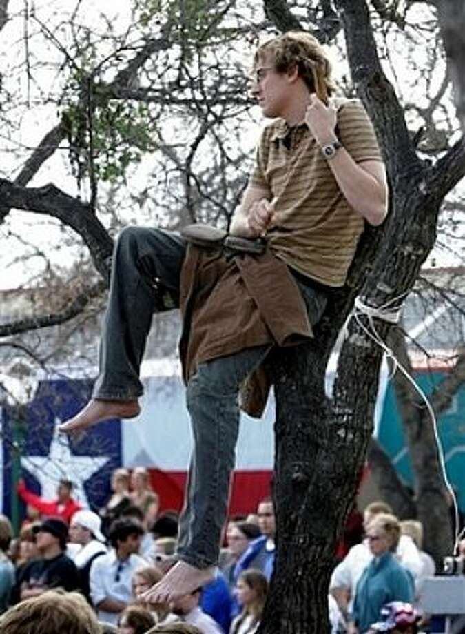 A supporter of Democratic presidential hopeful Sen. Barack Obama, D-Ill., watches from a tree during a town hall meeting in San Antonio, Tuesday, Feb. 19, 2008. (AP Photo/Eric Gay) Photo: Eric Gay, AP / AP